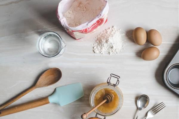 une table, de la farine, des oeufs, des ustensiles de cuisine et de la confiture. gluten ou no gluten