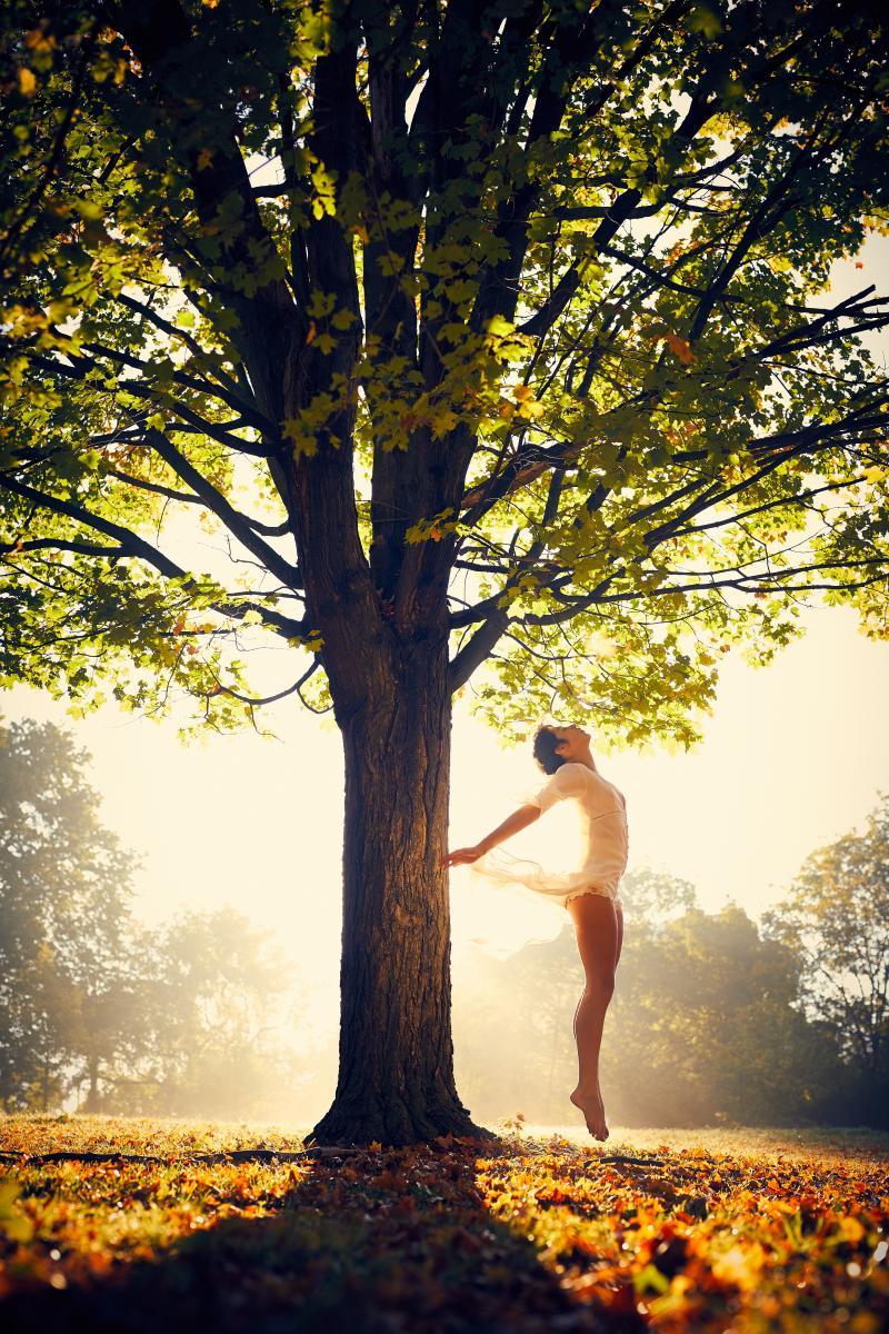 une femme saute en dessous un arbre, ménopause, réflexes santé