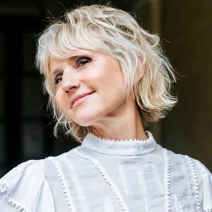 femme blonde souriante avec la tête penchée vers l'arrière